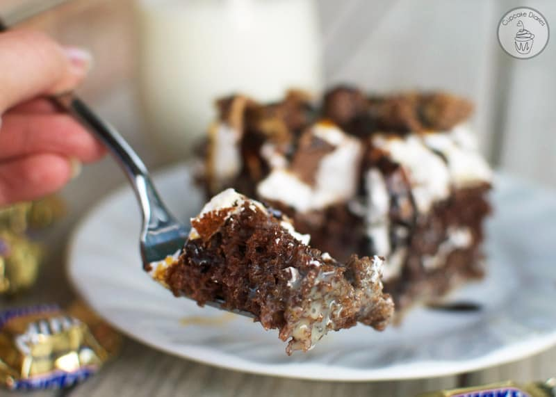 Snickers Poke Cake - This cake is so moist and decadent with chewy Snicker bars on top. This cake is amazing!