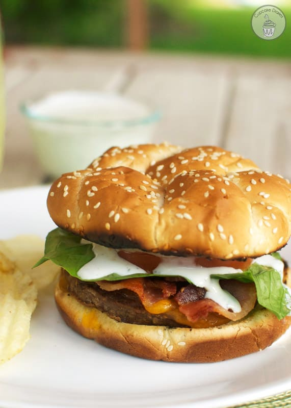Bacon Ranch Burger - A juicy cheeseburger topped with crispy bacon and a tangy ranch dressing. Perfect for a summer BBQ!