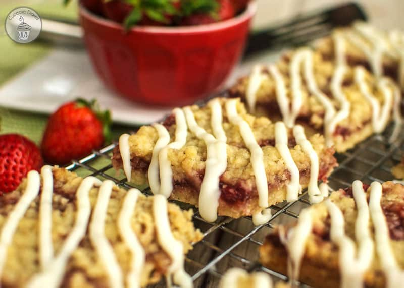 Strawberry Crumb Bars - A crispy cookie crust layered with sweet strawberries, buttery crumble, and a white chocolate glaze. A perfect summer dessert!