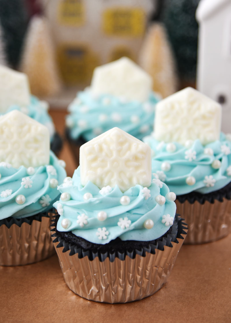 A chocolate cupcake topped with a smooth buttercream frosting and a white chocolate snowflake.
