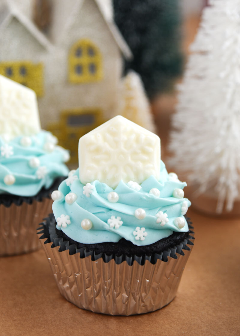 Snowflake Cupcakes for a Frozen themed party or wintertime treat! Each cupcake is topped with winter sprinkles and a solid white chocolate snowflake.