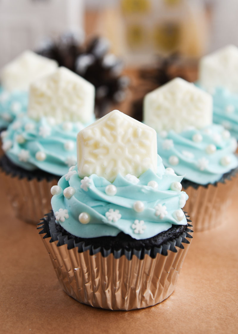 Beautiful chocolate cupcakes are topped with a buttercream frosting tinted ice blue and a solid white chocolate snowflake!
